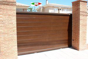 Puerta automática corredera en DURALUMINIO T-6 INOXIDABLE. Bastidor de 50x80x3.50 mm de sección. Imitación madera y marco decorativo de 1/2 caña. Cara exterior e interior de igual acabado,